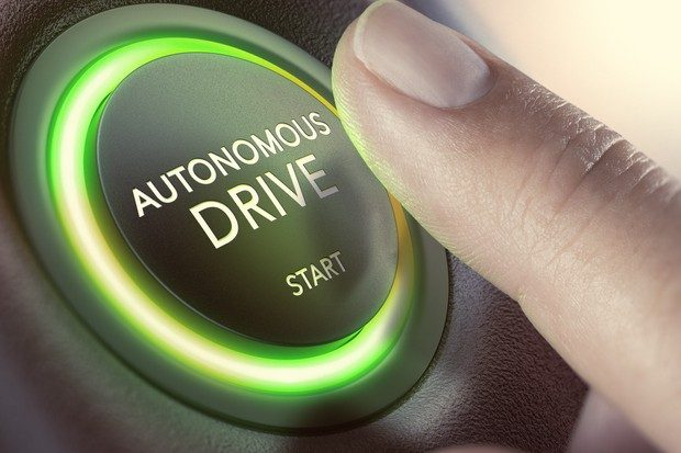 Vehicle ignition start button with the words 'Autonomous Drive - Start' with a finger hovering over the button to start the vehicle.
