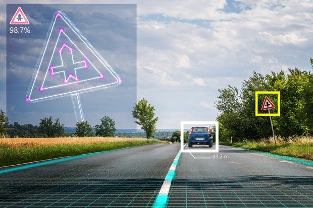 Computer view of a car on the road and a junction road sign. The car and road signs are in identifier boxes showing what the computer is seeing.